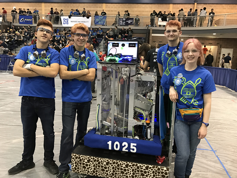 Impi warrior robotics team members posing with one of their robots