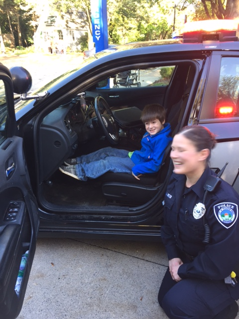 Child sits in the police car and hears the siren