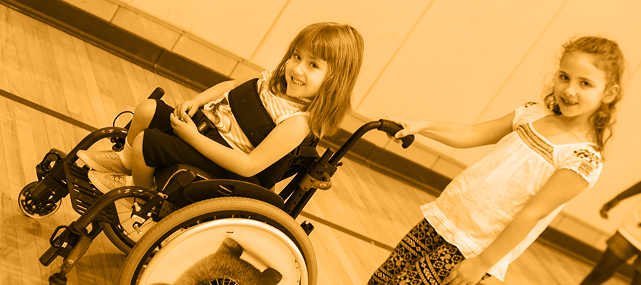 An elementary student in a wheelchair playing with another elementary student